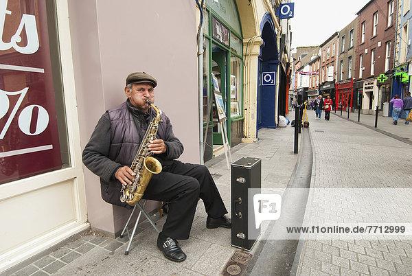 A Man Plays A Saxophone Along A Street  Ireland
