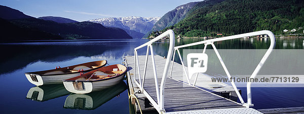 Row Boats By Jetty On Lake By Mountains