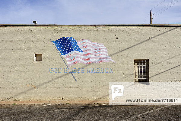 God bless america and flag mural on side of plain building Winslow arizona usa