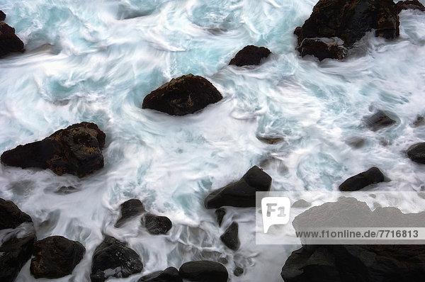 Black Volcanic Rocks In Sea