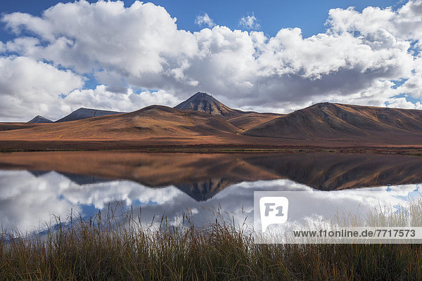 The mountains along the dempster highway reflected in an unnamed pond in autumn Yukon canada