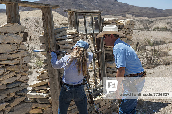 Male Instructor Guides Young Woman About How To Fire Shotgun At Lajitas Resort  Big Bend National Park And Big Bend State Park  South West Texas  Usa