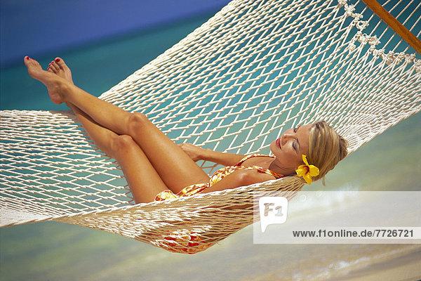 Europäer Frau liegend liegen liegt liegendes liegender liegende daliegen Strand geschlossen Beleuchtung Licht Küste Hängematte vorwärts