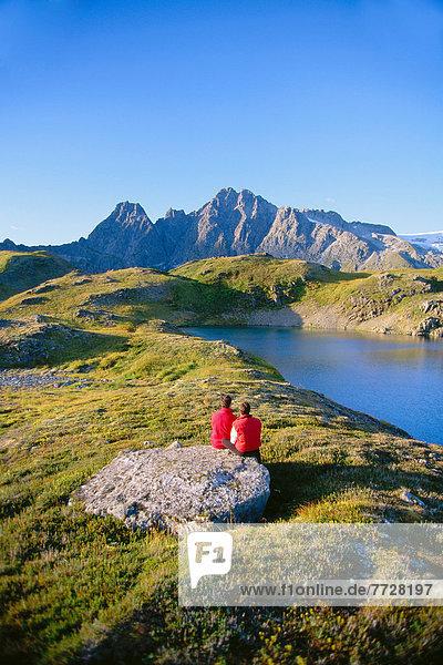blauer Himmel  wolkenloser Himmel  wolkenlos  sitzend  nebeneinander  neben  Seite an Seite  Berg  See  Ansicht  bedecken  Alaska  Juneau  Schnee