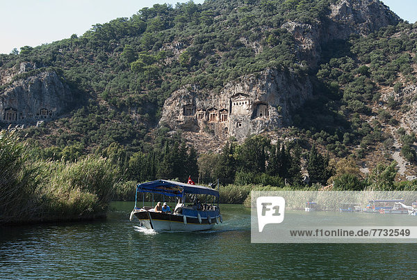 Small tourist boat passing Lycian style Kings Tombs on Dalyan River  Dalyan  Turkey