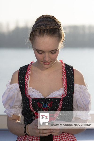 Teenagerin im Dirndl mit Handy  Lichtenau  Baden-Württemberg  Deutschland  Europa