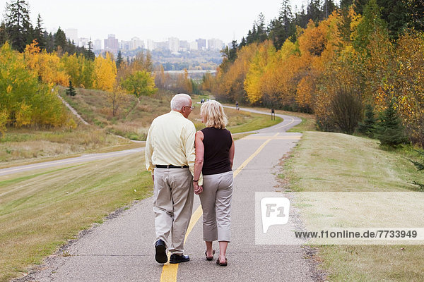 Mature Married Couple Walking Together In Park During Fall Season  Edmonton  Alberta  Canada