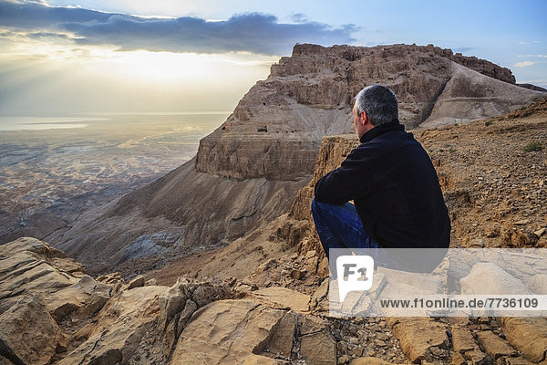 A Man Sits On A Rock Looking Out Over The Judean Desert  Israel