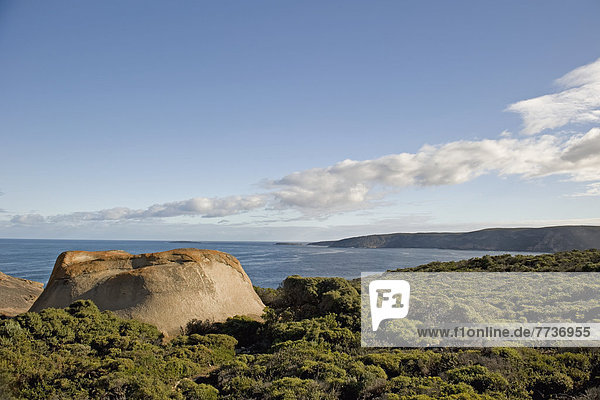 A large rock formation on the shore along the coast  australia