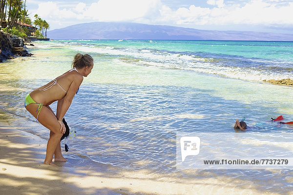 A mother watches her son snorkelling in the shallow water at the beach Hawaii united states of america