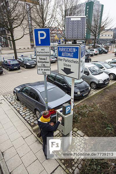 Frau löst Parkticket an Parkscheinautomat  innerstädtischer öffentlicher Parkplatz