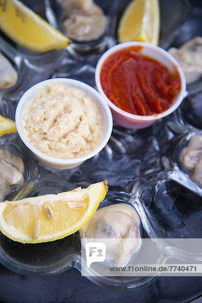Frische rohe Austernschale mit Zitrone  Meerrettich und Cocktailsauce in der Schüssel