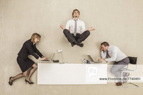 Geschäftsmann meditiert über dem Schreibtisch  während andere arbeiten.