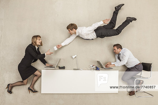 Geschäftsleute  die arbeiten  während ein anderer Geschäftsmann einen Becher zur Verfügung stellt.