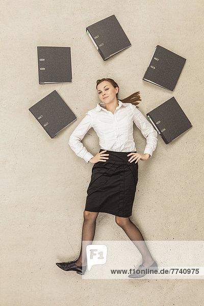 Geschäftsfrau steht um Akten herum