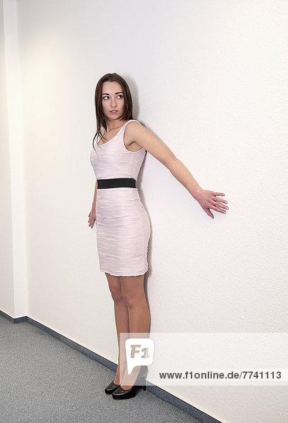 Geschäftsfrau an der Wand stehend  wegschauend