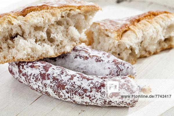Weißbrot mit Salami auf Holztablett  Nahaufnahme