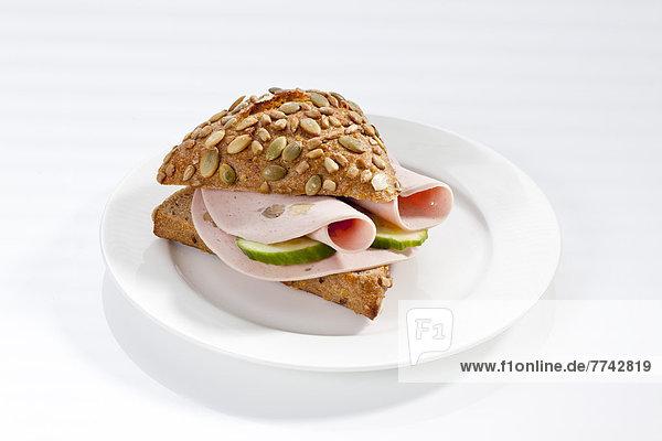 Sandwich aus Vollkornbrot mit Mortadella und Champignons auf dem Teller  Nahaufnahme