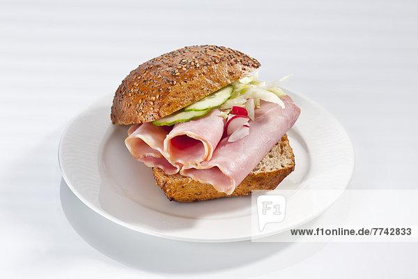 Sandwich aus Vollkornbrötchen mit Schinken auf Teller  Nahaufnahme
