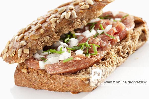 Sandwich aus Kornbrötchen mit gemahlenem Schinken auf weißem Grund  Nahaufnahme