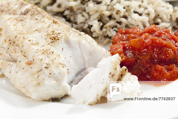 Teller gebratener frischer Hecht mit gekochtem Reis und Tomatendip  Nahaufnahme