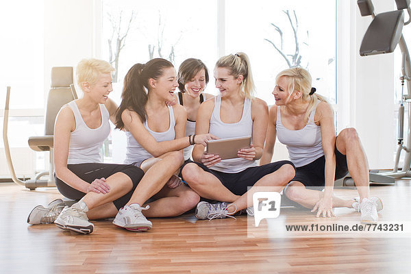 Frauen mit digitalem Tablett im Fitnessstudio  lächelnd