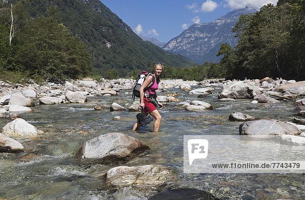Europa  Schweiz  Reife Frau beim Wandern am Verzasca Fluss