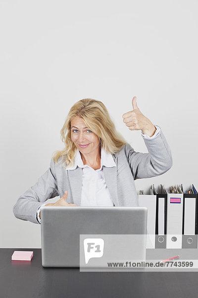 Portrait der Geschäftsfrau mit Laptop und Daumen hoch  lächelnd