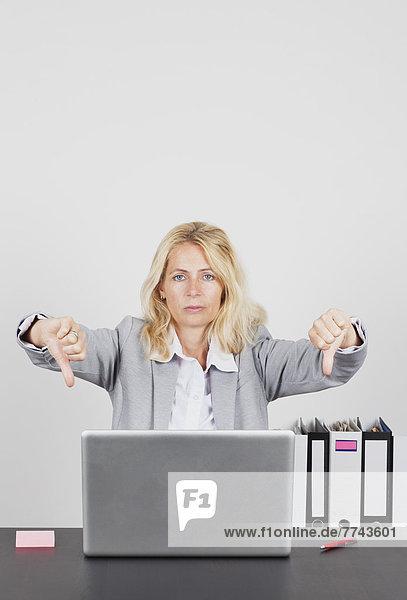 Porträt einer Geschäftsfrau mit Laptop und Daumen nach unten