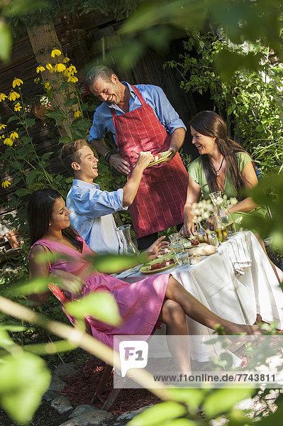 Österreich  Land Salzburg  Mann im Dienst seiner Familie im Garten