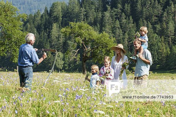 Deutschland  Salzburg  Bauer und Familie auf der Sommerwiese  lächelnd
