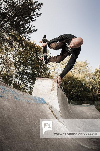Deutschland,  Nordrhein-Westfalen,  Düsseldorf,  Reife Männer springen mit Skateboard