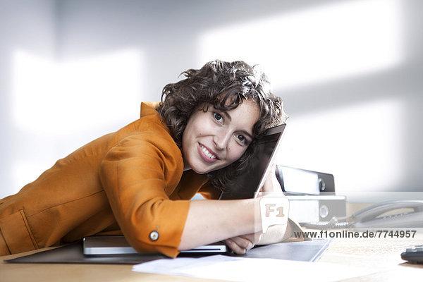 Geschäftsfrau umarmt Laptop im Büro  lächelnd  Portrait