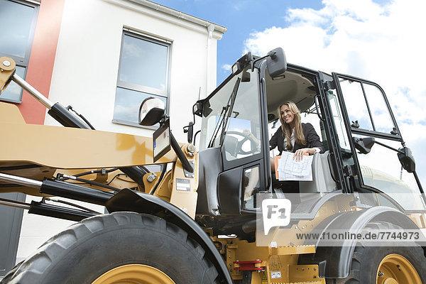 Deutschland  Neuss  Immobilienmakler mit Radlader auf der Baustelle