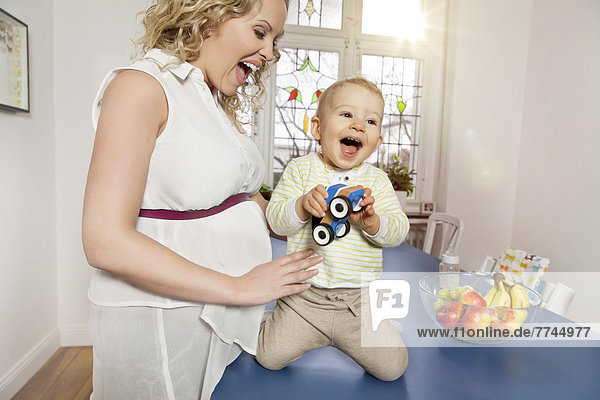 Germany  Bonn  Pregnant mother playing with son in living room  smiling