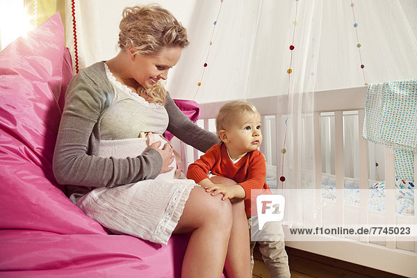 Germany  Bonn  Pregnant mother explaining her belly to son  smiling