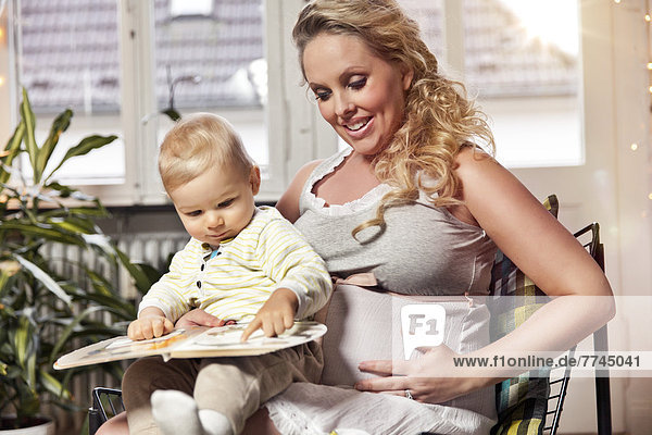 Germany  Bonn  Pregnant mother reading book to son in living room  smiling