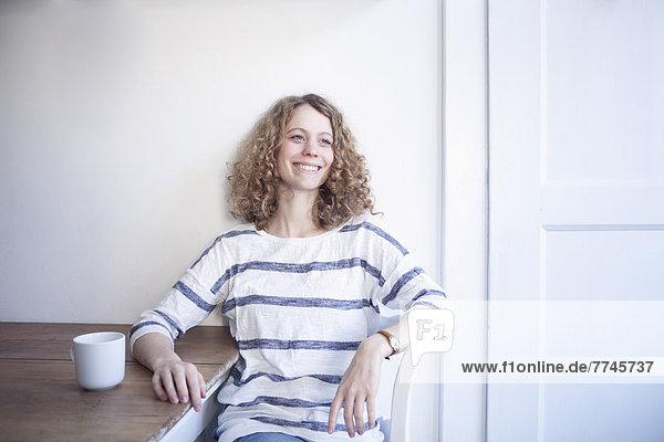 Porträt einer jungen Frau am Tisch sitzend  lächelnd