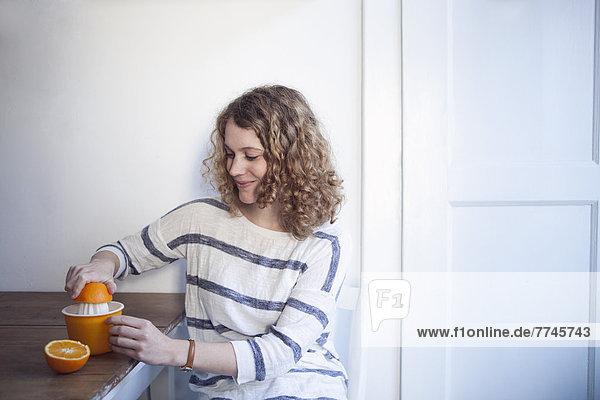 Junge Frau sitzt am Tisch und drückt Orange auf den Entsafter  lächelnd