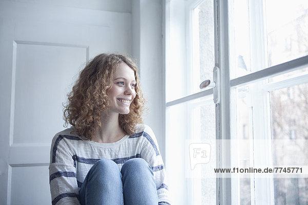 Junge Frau am Fenster sitzend  lächelnd