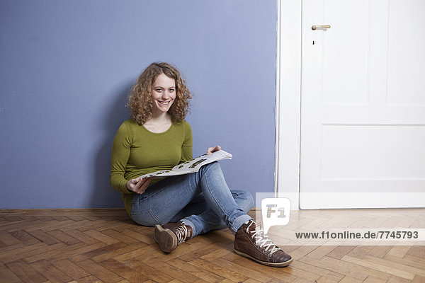 Young woman sitting on floor and reading magazine  smiling  portrait