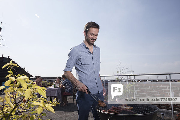 Man barbecueing on grill  smiling