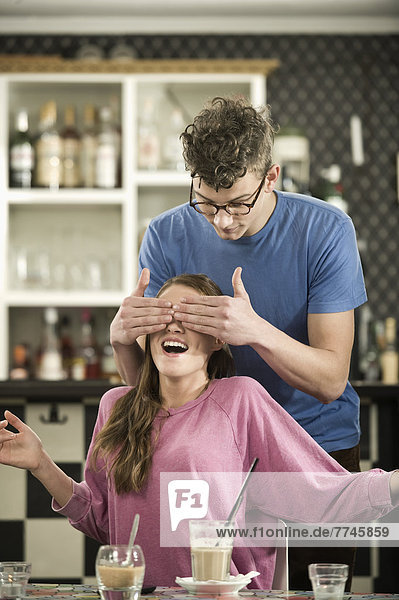 Mann bedeckt die Augen der Frau im Café