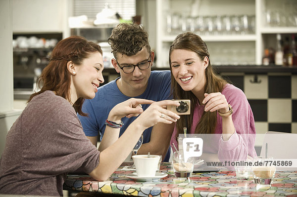 Deutschland  Bayern  München  Junge Freunde  die sich Bilder in der Kamera ansehen  lächelnd