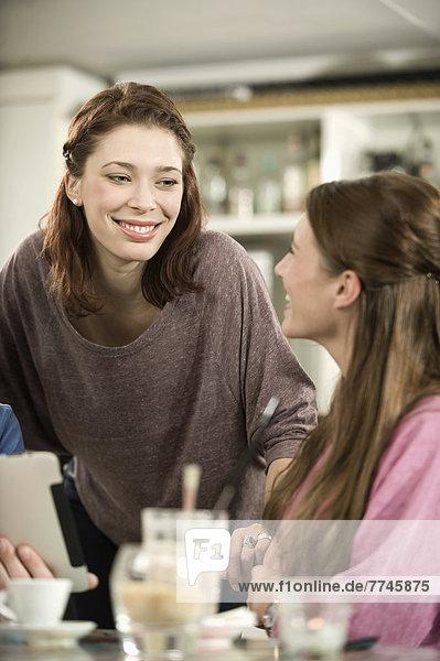 Deutschland  Bayern  München  Junge Freunde reden im Café  lächeln