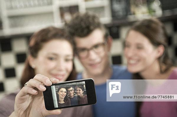 Deutschland  Bayern  München  Junge Freunde beim Fotografieren mit dem Handy im Café