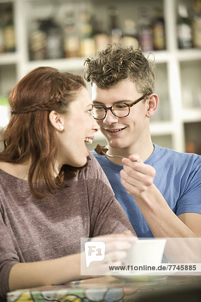 Young man feeding piece of cake to woman in cake