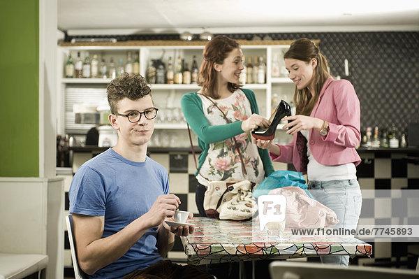 Junger Mann  der sich langweilt  während Frauen gerne einkaufen gehen