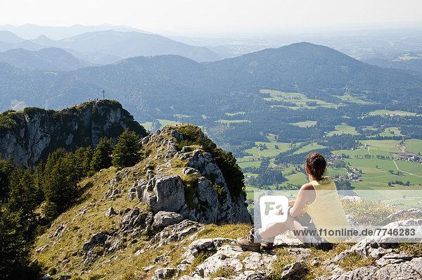 Mittlere erwachsene Frau mit Blick von Breitensein auf die bayerischen Alpen