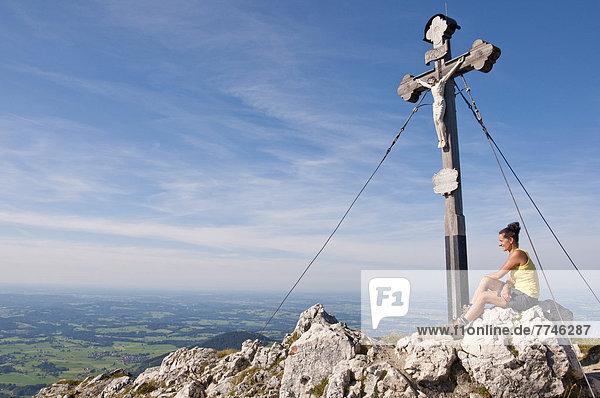 Mittlere erwachsene Frau sitzend auf Bergsummmit mit Kreuz